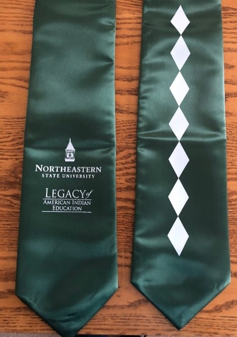 NSU American Indian Students A green stole with white NSU Legacy of American Indian Education logo on one side and a column of 7 white diamonds on the other